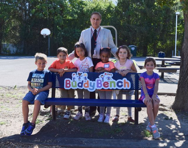 Adult man and 6 children on a bench with a sign that says Buddy Bench