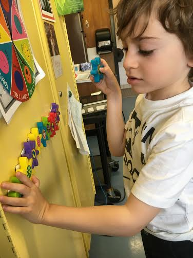boy playing with magnetic letters in the classroom