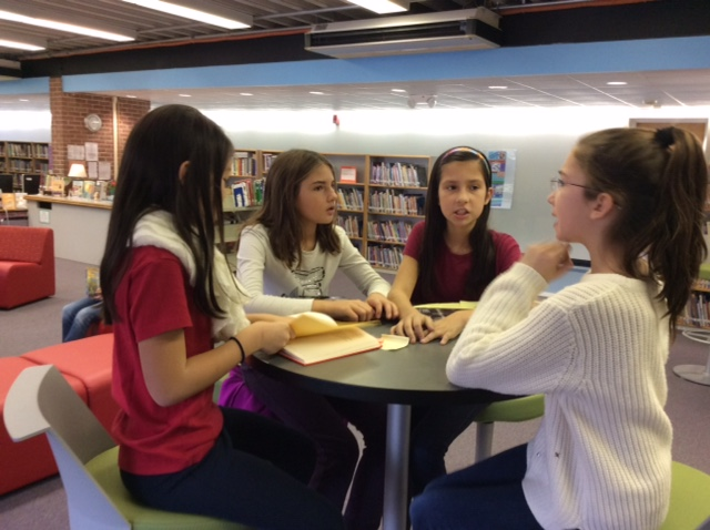 photo of four students sitting at a cafe table in the learning commons, discussing a book