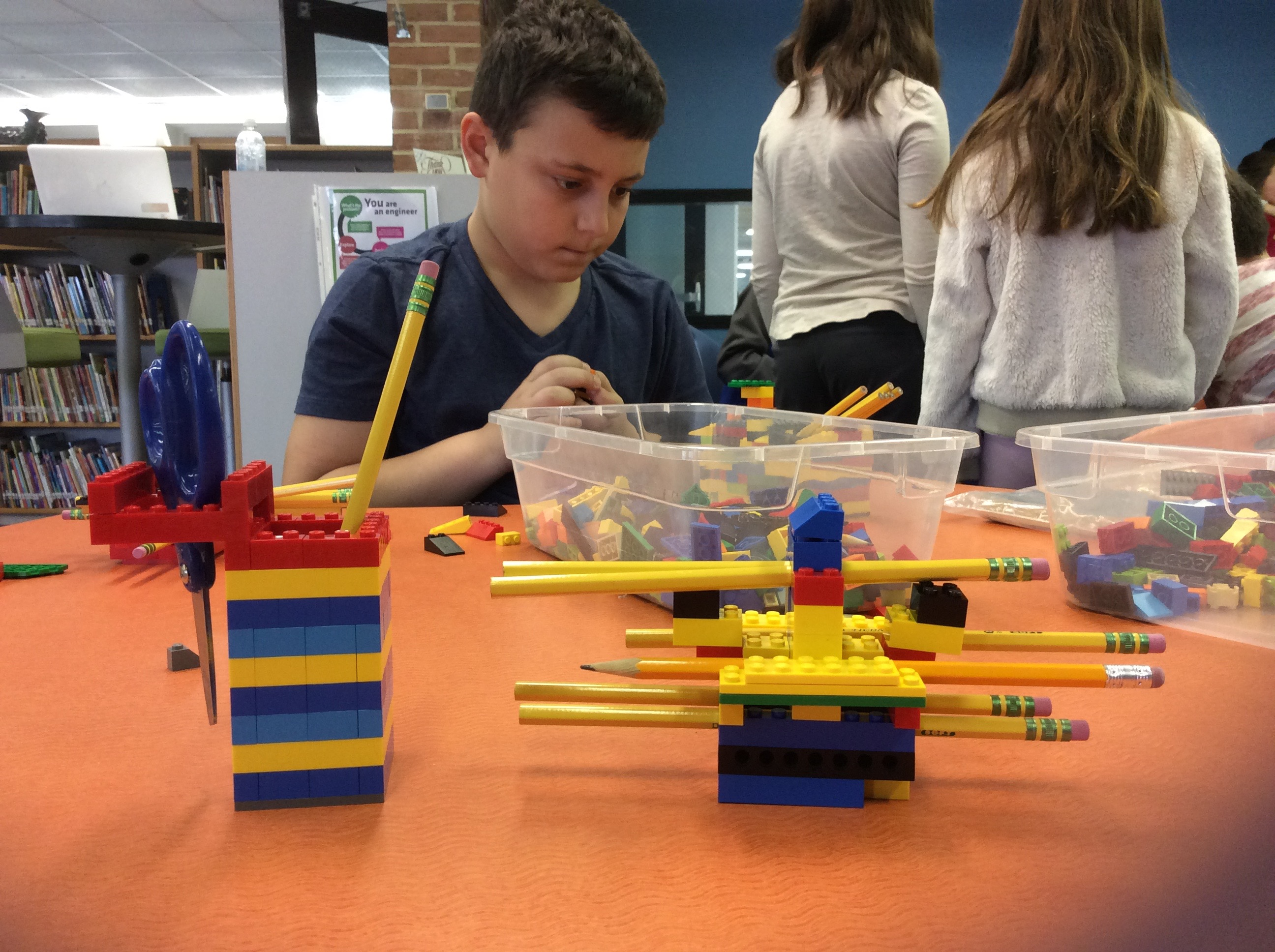 photo of a child building a pencil holder with legos